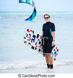 Female kiteboarder on the beach - Female kiteboarder...