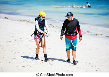 Kitesurfing instructor and female student preparing lines on...