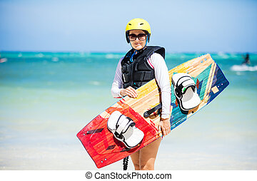 Wakeborder girl at the beach with her surfboard