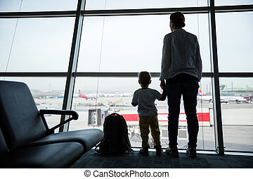 Mother and son standing near window in airport and watching...
