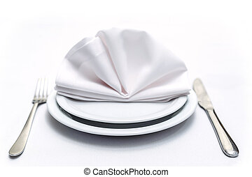 Place settings with two plates, one on one, napkin over...
