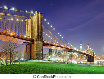 Brooklyn Bridge over East River at night in New York City Manhattan with green park