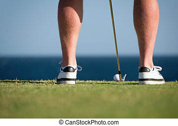 Golf ball and stick with golfer legs in the foreground in...