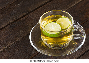 Hot lemon tea in glass on old wooden background.Close up