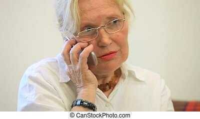 Old woman talking on phone - old woman is talking on the...