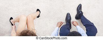 Interracial couple putting on shoes