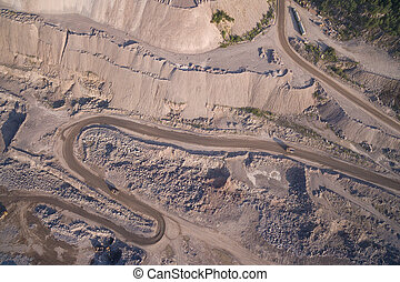 Industrial trucks moves along the road in the sand quarry -...