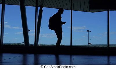 Young man with a backpack standing in an airport lounge and...