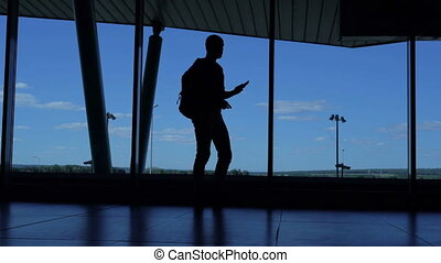Young man with a backpack standing in an airport lounge and talking on the phone.