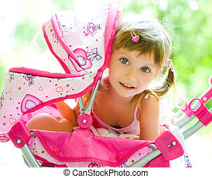 Child with toy carriage - Cute little girl with her toy...