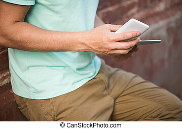 Close up of a man using mobile smart phone and tablet, focus on hand