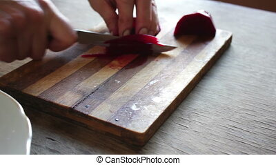 Cutting beet on a board chef cooking - woman cuts red beet...
