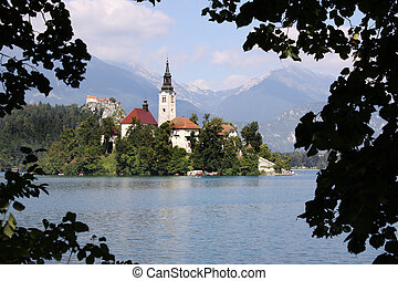 Lake Bled Island Church framed by some trees on the mainland...