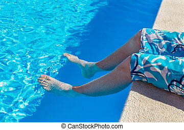 Teenage boy holding bare legs in blue swimming pool on...