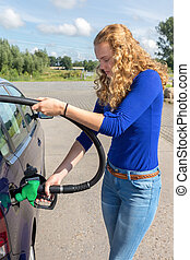 Young woman fueling car tank with gasoline