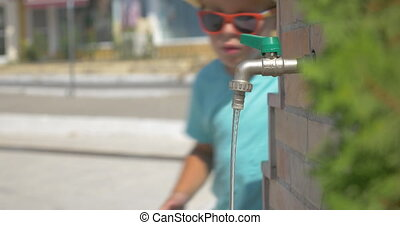 boy washing your hands in fountain faucet in public place at summer day Piraeus, Greece