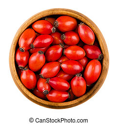 Red rose hips in a wooden bowl