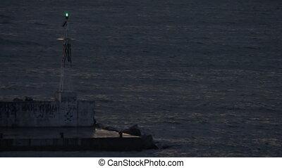 In Nea Kallikratia, Greece in night sea is lighthouse and...