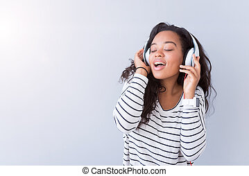Joyful content woman listening to music - Feel the beat....