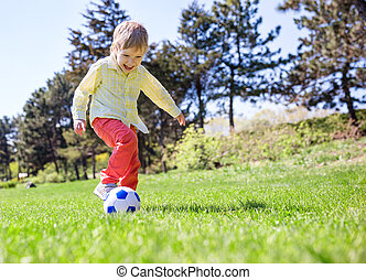 Happy young boy playing football outdoors
