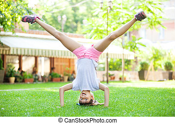 Young girl performing headstand in park