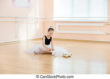 Young ballerina changing dancing shoes to pointe ones while...