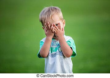 Little boy playing peek-a-boo outdoors