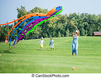 Happy family flying kite together on a green field