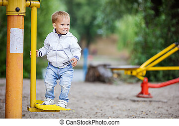 Happy toddler boy playing in park - Happy toddler boy...