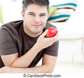 Positive man holding a red apple