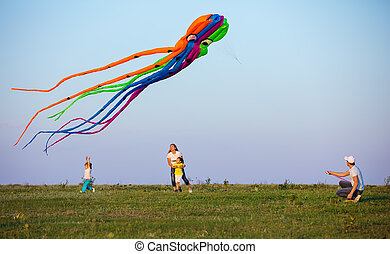 Family flying kite together on green field