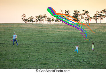 Father and two sons flying kite