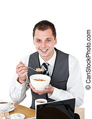 Young businessman eating cereals looking at his laptop...