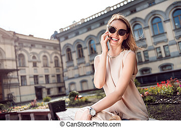 Cute young woman using phone - Staying in touch. Happy and...