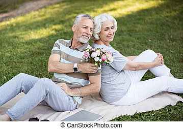 Happy aged married couple sitting on the grass in park -...