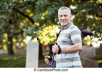 Handsome sporty grandfather outside his house