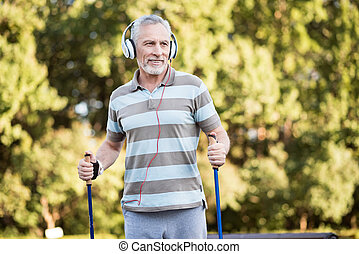 Senior citizen listening to music while walking in the park