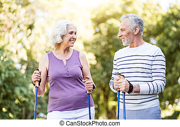 Retired man and woman smiling at each other in love - Bright...