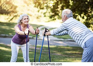 Grandparents doing morning exercises in their garden