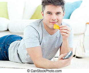 Relaxed young man eating crisps holding a remote