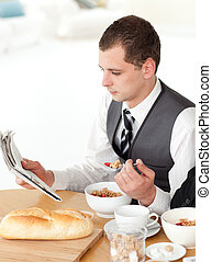 Businessman eating cereals while reading the news against...