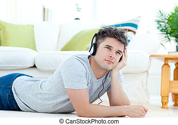 Young man with headphones lying on the floor in the living...