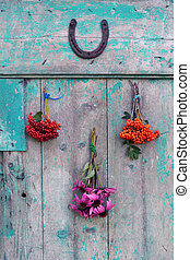 Bunches of herbs and berries with horseshoe on door -...