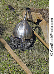 Knight armor headpiece and weapons on grass at medieval...
