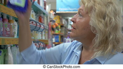 Close up view of senior woman is choosing cleanser in a bottle at supermarket and reading package for cleaning