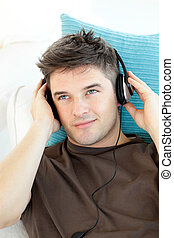 Smiling young man with headphones listening to music lying...