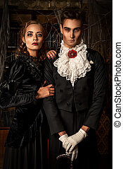 gothic pair - Beautiful man and woman vampires dressed in...