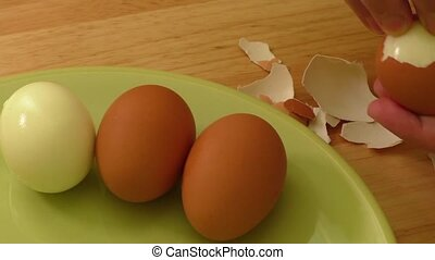 Hands peeling boiled egg