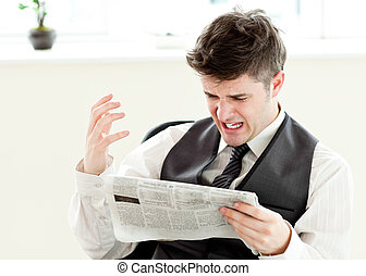 Portrait of a annoyed businessman reading a newspaper in the...