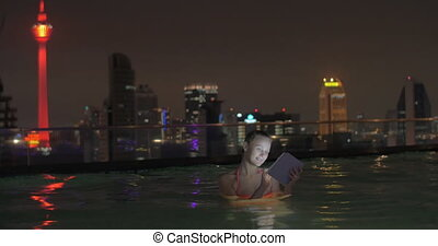 In pool on roof of a hotel in Kuala Lumpur, Malaysia is swimming young girl and works on tablet